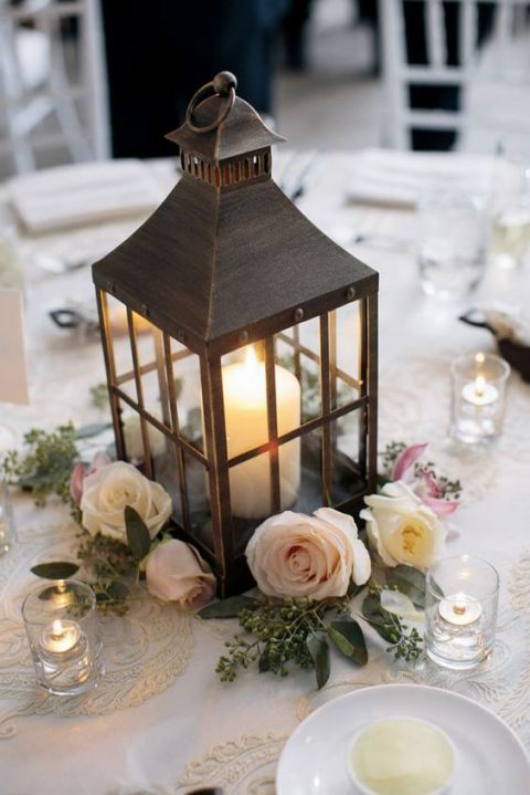 a candle lantern with neutral blooms