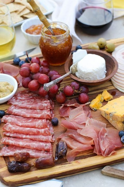 a charcuterie board with various types of cheese, fruits and honey