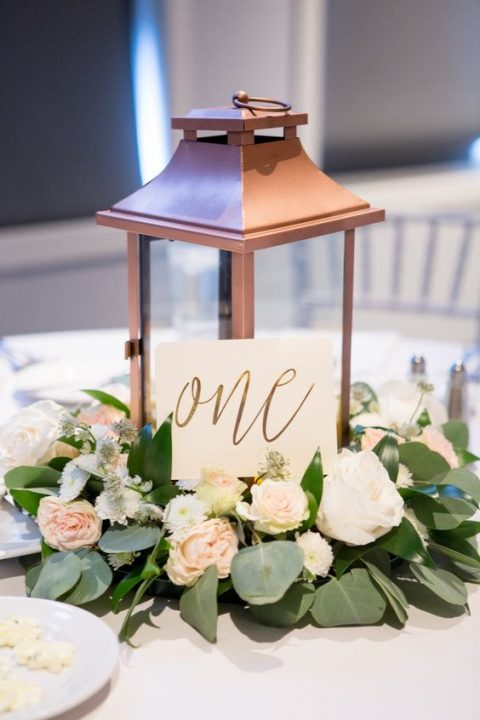a copper candle lantern with a calligraphy table number, blush blooms and greenery