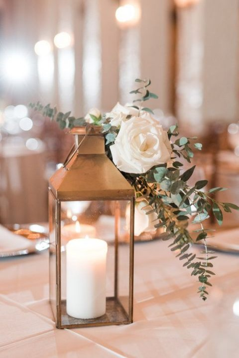 a copper candle lantern with a white rose and eucalyptus on top