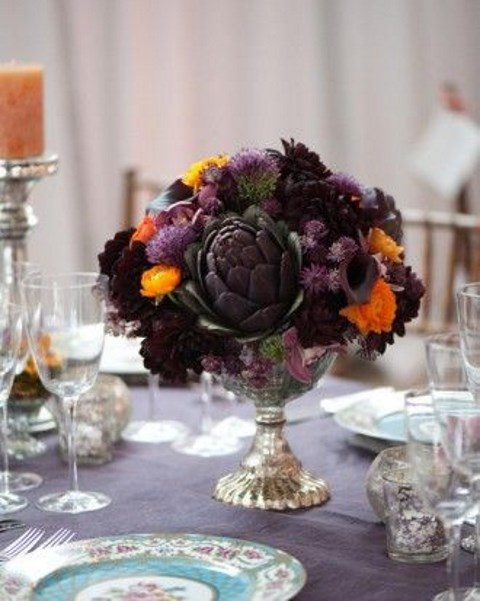 a dark centerpiece with an artichoke, deep purple and orange blooms