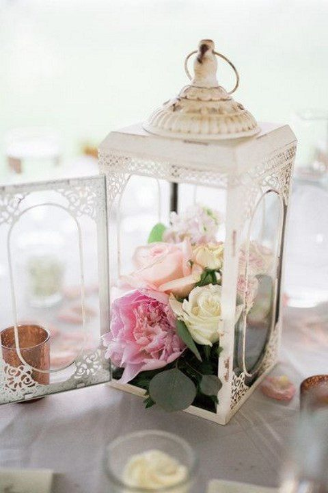 a delicate white lantern with pink and neutral flowers inside