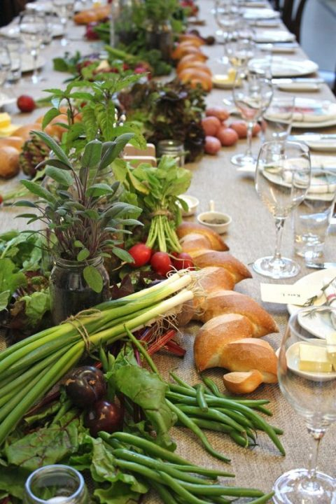 a fam-styled table runner with onion, radish, plums and herbs