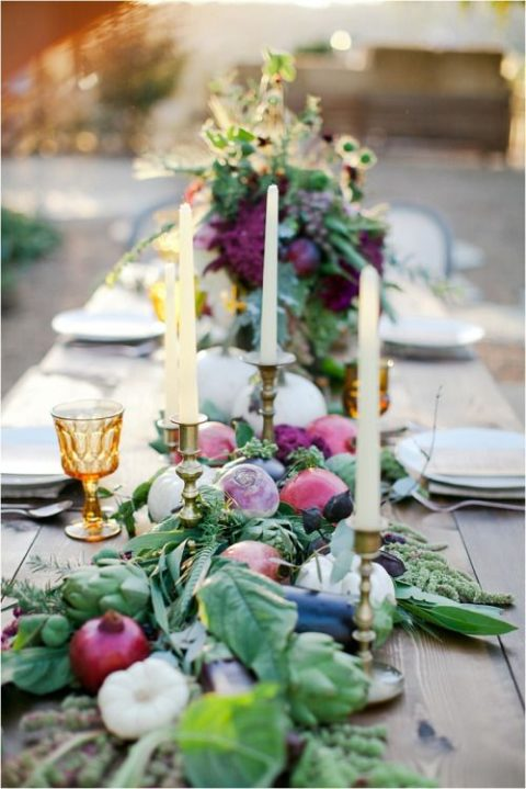 a farm-styled table runner with pomegranates, artichokes, onions, leaves, garlic