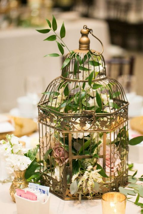 a gilded bird cage with foliage and pastel florals