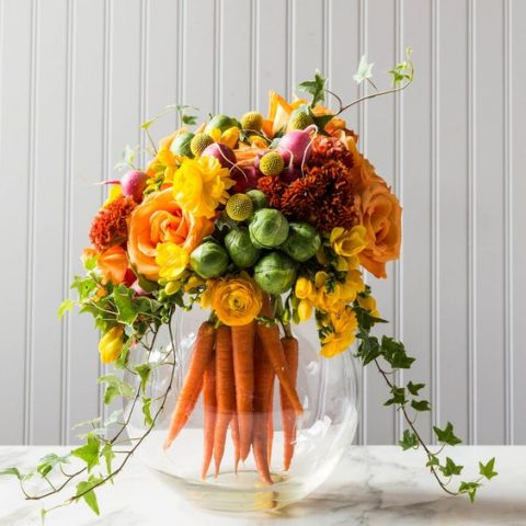 a glass aquarium with carrots, cabbages, radish and fall-inspired blooms