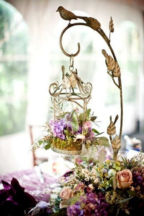 a hung bird cage with moss and flowers for an enchanted garden wedding