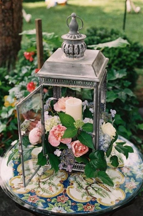 a lantern with a candle and filled with peachy blooms and greenery