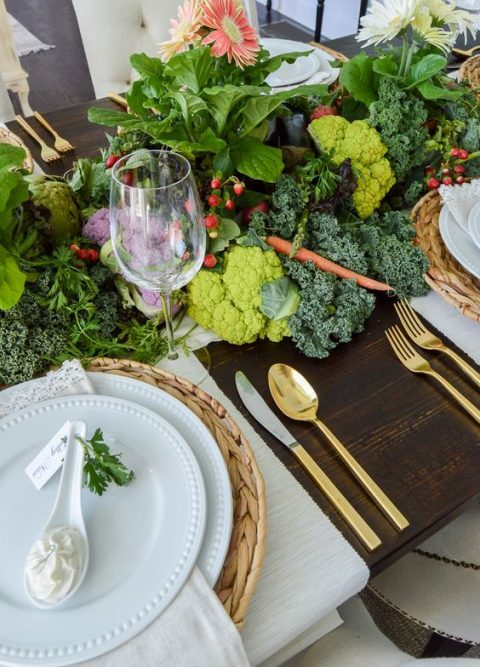 a lush table runner with broccoli, radish, berries, leaves and blooms