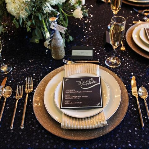 a navy sequin tablecloth and gold and glitter cutlery and plates