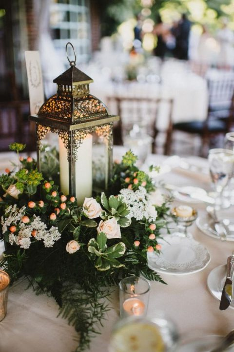 a refined candle lantern with lush greenery, foliage and neutral blooms