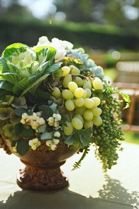 a rustic urn with grapes, greenery and cabbage for a rustic fall wedding