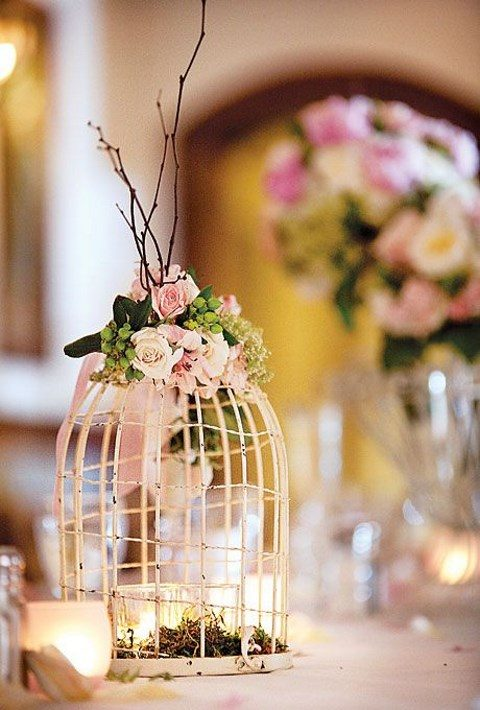 a shabby chic bird cage with candles and moss inside and a bold floral arrangement on top