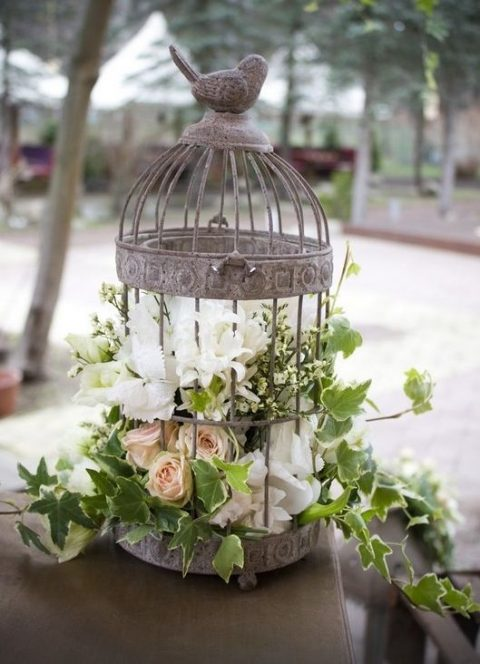 a shabby chic bird cage with lush white and blush florals