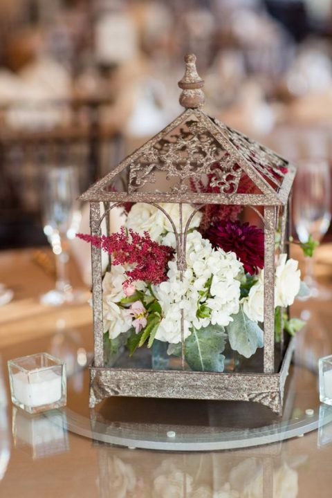 a shabby chic cage with a floral arrangement inside