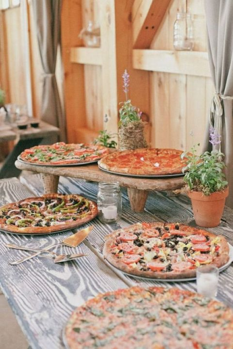 a simple rustic pizza station with wooden stands and potted herbs