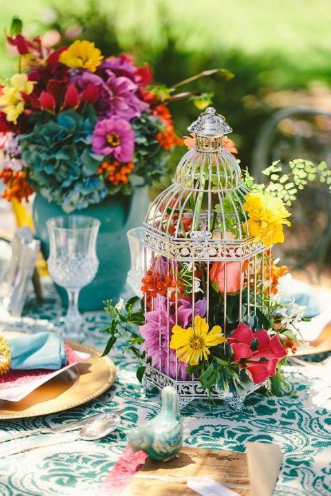 a small bird cage with bold lush florals for a colorful wedding