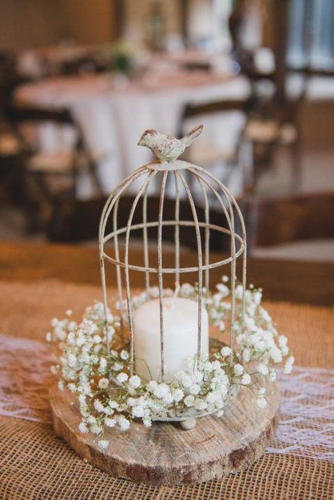 a small cage with a candle, baby's breath placed on a wooden slice