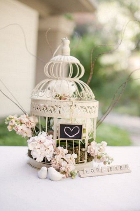a small white cage with pastel and neutral florals and a chalkboard sign