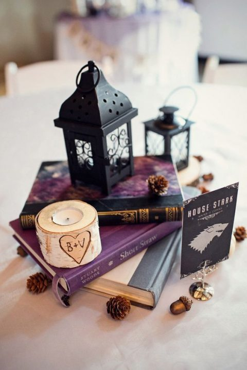 a stack of books with a black candle lantern, pinecones and a birch candle holder