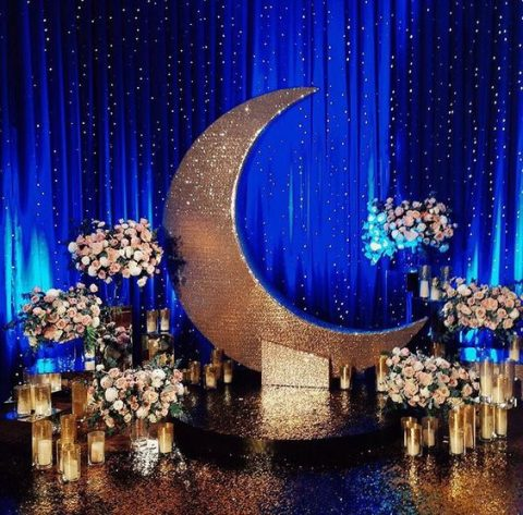 a stunning starry night-themed wedidng ceremony space with lots of candles, lush florals and lights