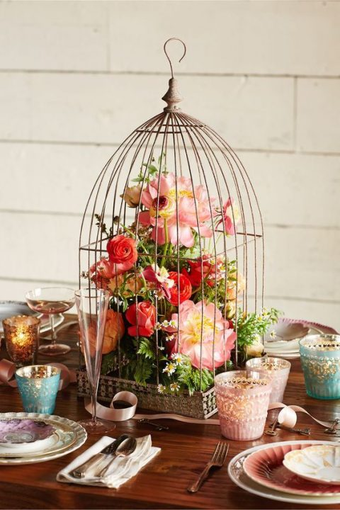 a tall bird cage with a bold floral arrnagement