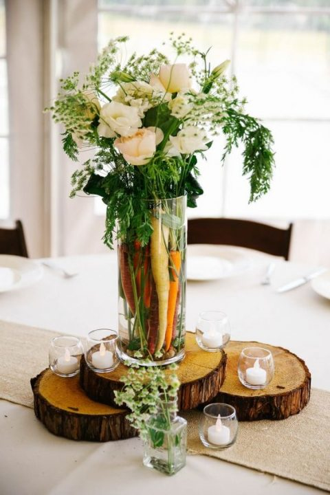 a tall vase with carrots and white flowers and herbs for a rustic wedding