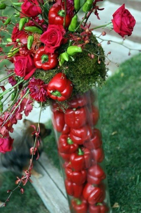 a tall vase with red peppers, red roses and moss