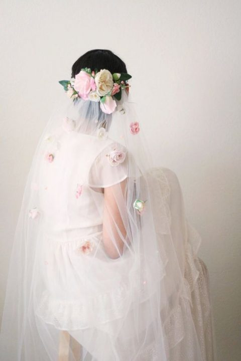 a veil with pink flowers and a floral headpiece
