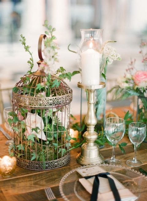 a vintage bird cage with lush foliage and blush blooms