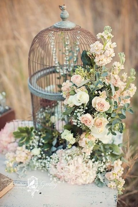 a vintage cage decorated with lush florals on the side and crystal strands