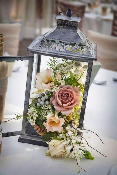 a vintage lantern filled with blooms and greenery