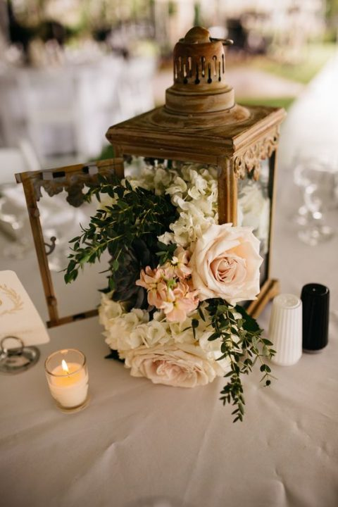 a vintage lantern with lush neutral and blush blooms and greenery
