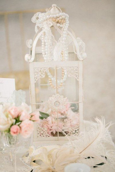 a vintage white lantern with pink blooms and pearl strands on top