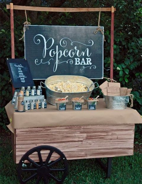a vitnage popcorn bar with a chalkboard sign and various toppings