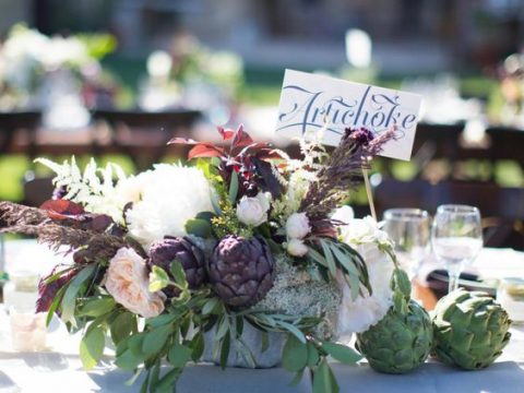 a wedding centerpiece with artichokes, blooms and leaves