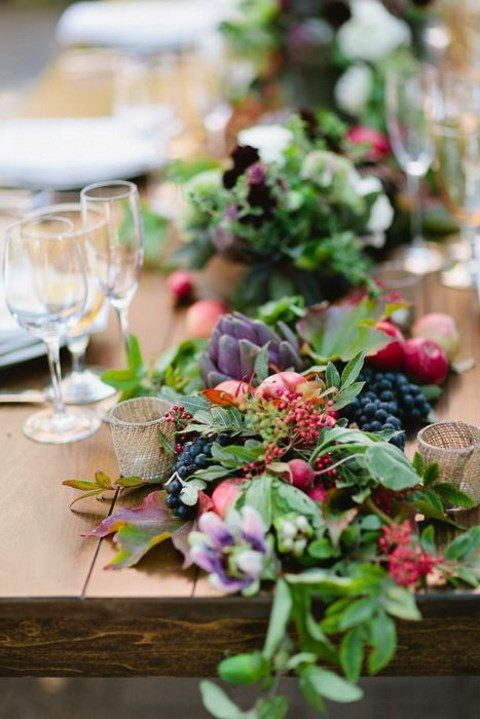 a wedding table runner with foliage, berries and artichokes for a fall wedding