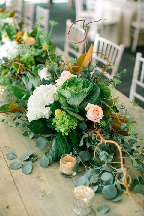 a wedding table runner with leaves, blush and neutral flowers, cabbages and herbs