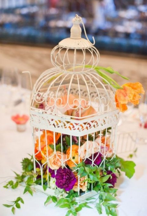 a white bird cage filled with foliage and bold blooms