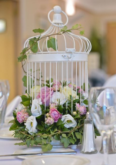 a white bird cage filled with white and pink blooms