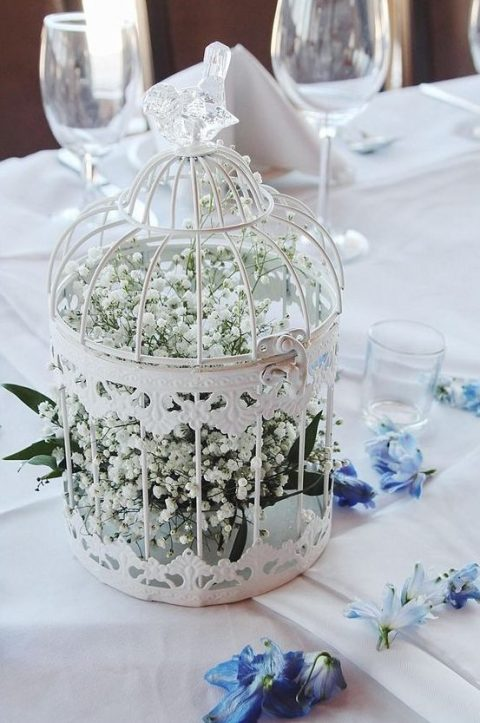 a white bird cage with a crystal bird on top filled with baby's breath