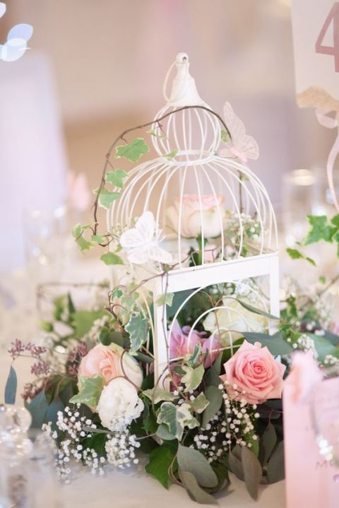 a white bird cage with lush foliage and pink and blush blooms