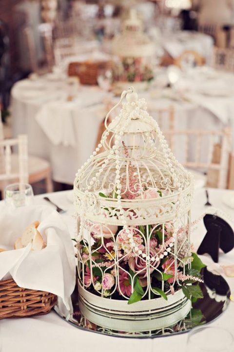 a white bird cage with pink florals and pearl strands on top
