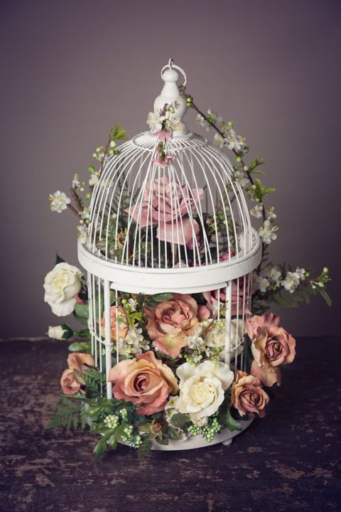 a white cage filled with fresh blooms and greenery