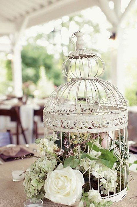 a white cage with greenery and blooms looks cute and chic
