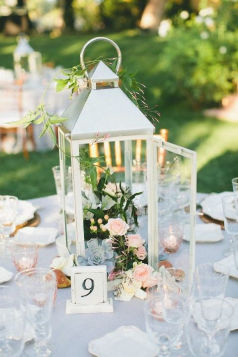 a white candle lantern with blush roses, greenery and pale succulents