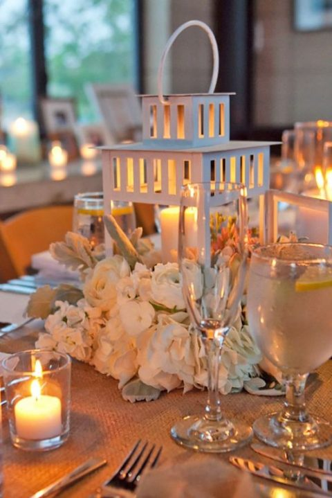 a white candle lantern with neutral blooms around