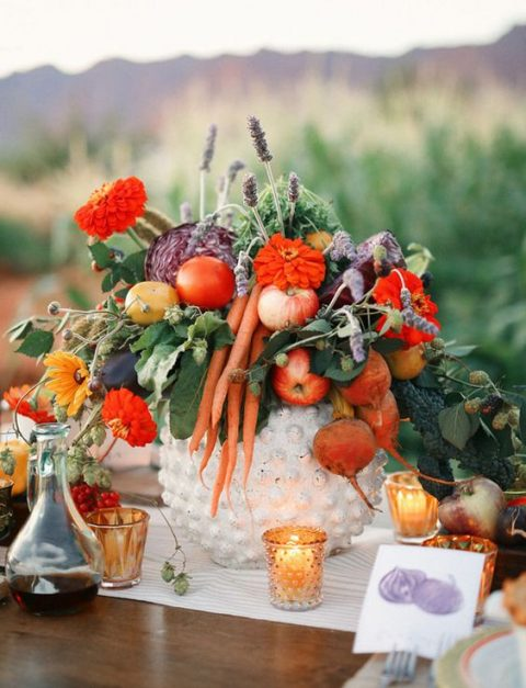 a white urn with apples, carrots, cabbage, citrus, lavender and red blooms
