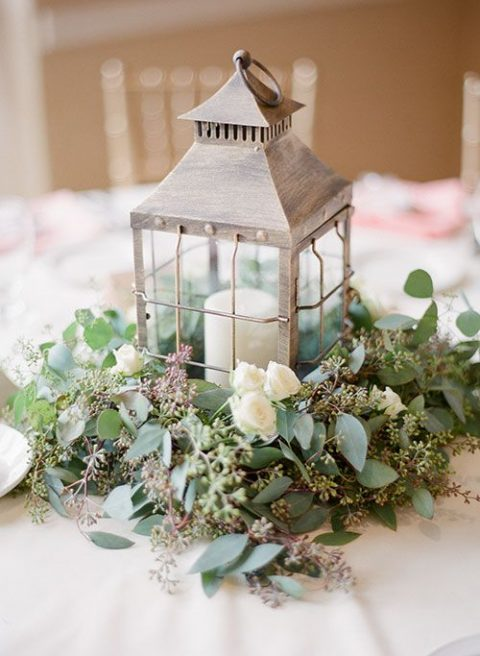 a whitewashed candle lantern with greenery and white blooms