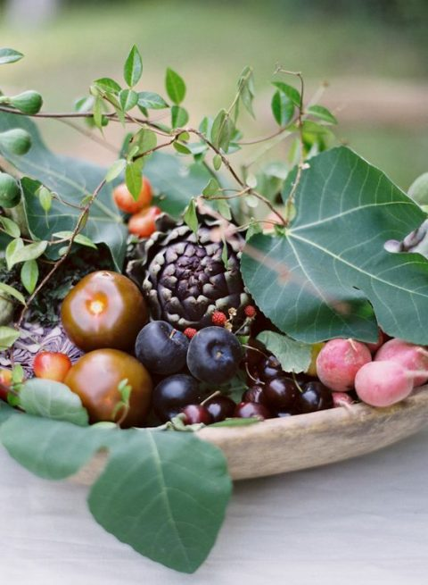 a wooden bowl with various fruits and artichokes for a fall wedding